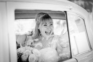 Happy bride waving inside wedding car